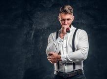 Nachdenkliches männliches, ungefähr etwas denkend wichtig Stilvoll gekleideter junger Mann im Hemd mit der Fliegen- und Hosenträg lizenzfreies stockfoto