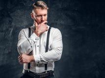 Nachdenkliches männliches, ungefähr etwas denkend wichtig Stilvoll gekleideter junger Mann im Hemd mit der Fliegen- und Hosenträg lizenzfreie stockfotografie