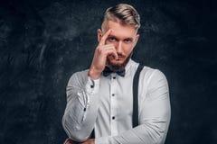 Nachdenkliches männliches, ungefähr etwas denkend wichtig Stilvoll gekleideter junger Mann im Hemd mit der Fliegen- und Hosenträg stockfoto