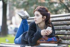Nachdenkliches schönes Mädchen, das auf Bank, Adoleszenzlebensstilbetrüger liegt Stockfoto