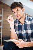 Nachdenkliches Schreiben des jungen Mannes im Notizblock und zu Hause denken Stockbild