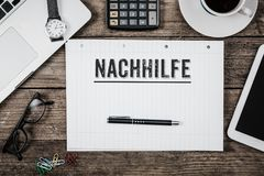 Nachhilfe German for private lessons on notepad Royalty Free Stock Images