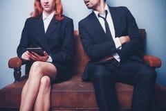 Nachlässiger Geschäftsmann, der auf erfolgreichem weiblichem Mitarbeiter ausspioniert Stockfotografie