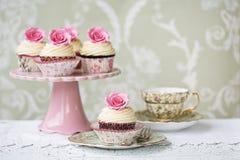 Nachmittagstee mit rosafarbenen kleinen Kuchen Stockfotografie
