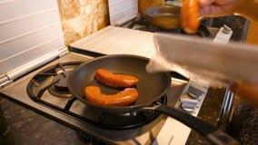 Putting Raw Sausage Links into Hot Pan to Cook