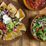 Nacho Cheese Tortilla chips with chili and salsa Royalty Free Stock Image