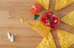Nacho chip in salsa dip on cutting board. And scattered around crumbs, garlic, parsley and half of cherry tomato Stock Photo