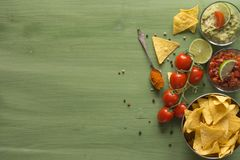 Nacho chips arranged on green wooden surface. Nacho chips arranged on green colored wooden surface with lime, tomato, a spoon with paprika powder, a bowl of Stock Photography