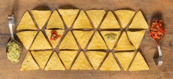 Nacho chips arranged on wooden surface. With some seasoning guacamole and salsa royalty free stock photo