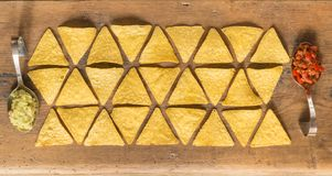 Nacho chips arranged on wooden surface. Nacho chips flat lay top view on wooden surface Royalty Free Stock Images