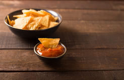 Nacho chips. Mexican nacho chips and salsa dip in bowl on wooden background Stock Photos