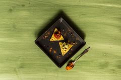Nacho chips arranged on green wooden surface. Nacho chips on a plate arranged on green colored wooden surface with some seasoning guacamole and salsa Stock Images