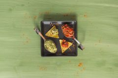 Nacho chips arranged on green wooden surface. Nacho chips on a plate arranged on green colored wooden surface with some seasoning guacamole and salsa Royalty Free Stock Images