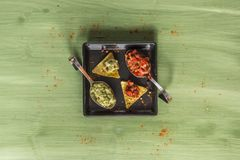 Nacho chips arranged on green wooden surface. Nacho chips on a plate arranged on green colored wooden surface with some seasoning guacamole and salsa royalty free stock photos