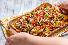 Nacho corn tortilla chips with cheese, meat, guacamole and red hot spicy salsa Royalty Free Stock Images
