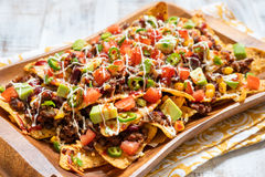 Nacho corn tortilla chips with cheese, meat, guacamole and red hot spicy salsa Stock Photos