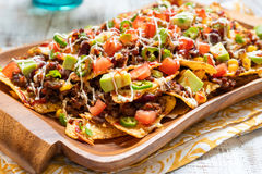 Nacho corn tortilla chips with cheese, meat, guacamole and red hot spicy salsa Royalty Free Stock Image
