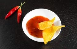 Nacho croccanti del cereale con salsa al pomodoro calda piccante come uno spuntino o aperitivo in un disco bianco Immagini Stock