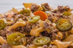 Nacho szczerbi się kukurudzy garnirującej z zmieloną wołowiną, rozciekły ser, jalapeños pieprzy meksykański korzenny jedzenie w  fotografia stock