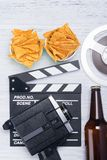 Nachos, öl och utrustning för att skjuta en film på en ljus bakgrund arkivfoto