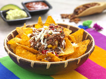 Nachos. A bowl with spicy tortilla chips served with minced meat and cheese stock photo