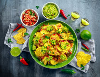 Nachos with cheese, jalapeno peppers, red onion, parsley, tomato, salsa, guacamole sauce and tequila on green plate. Nachos with cheese, jalapeno peppers, red royalty free stock image