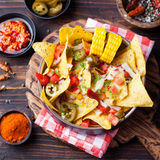 Nachos, cheese sauce, salsa and corn cobs Top view Stock Image