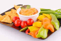 Nachos, cheese sauce,  vegetables Royalty Free Stock Photography