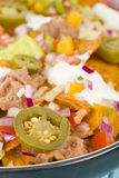 Nachos. Cheesy  topped with sour cream, refried beans, pico de gallo, jalapenos and guacamole Royalty Free Stock Photos