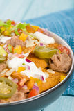 Nachos. Cheesy  topped with sour cream, refried beans, pico de gallo, jalapenos and guacamole Stock Photography