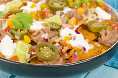 Nachos. Cheesy  topped with sour cream, refried beans, pico de gallo, jalapenos and guacamole Royalty Free Stock Photography
