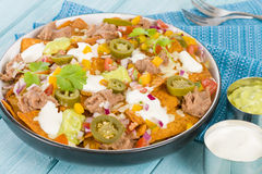 Nachos. Cheesy  topped with sour cream, refried beans, pico de gallo, jalapenos and guacamole Stock Image