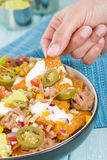 Nachos. Cheesy  topped with sour cream, refried beans, pico de gallo, jalapenos and guacamole Royalty Free Stock Images
