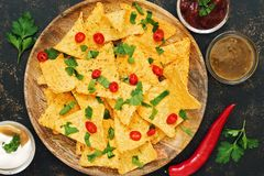 Nachos. Close-up of corn chips with variety of sauces ,chili pepper and greens on dark background. The view from the top, place fo royalty free stock image