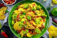 Nachos com queijo, pimentas do jalapeno, a cebola vermelha, a salsa, o tomate, a salsa, o molho do guacamole e o tequila na placa Fotos de Stock