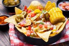 Nachos con la salsa de queso derretida, salsa, mazorcas de maíz Imágenes de archivo libres de regalías