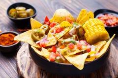 Nachos con la salsa de queso derretida, salsa, mazorcas de maíz Imagen de archivo