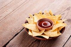 Nachos con la salsa en la tabla imagenes de archivo