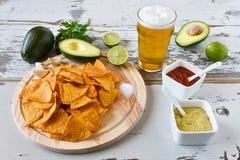 Nachos con las salsas cerveza y aguacate Fotos de archivo libres de regalías