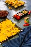 Nachos con salsa, la haba y la mostaza del tomate de los microprocesadores de tortilla en fondo de piedra rústico Un fondo textur fotografía de archivo