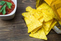 Nachos corn chips with classic tomato salsa. Fresh cold beer is perfect with savory snacks. Royalty Free Stock Photo