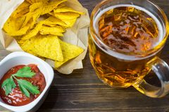 Nachos corn chips with classic tomato salsa. Fresh cold beer is perfect with savory snacks.  Royalty Free Stock Image