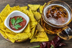 Nachos corn chips with classic tomato salsa. Fresh cold beer is perfect with savory snacks.  Stock Photography