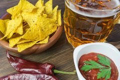 Nachos corn chips with classic tomato salsa. Fresh cold beer is perfect with savory snacks.  Royalty Free Stock Photography