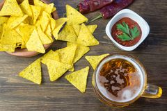 Nachos corn chips with classic tomato salsa. Fresh cold beer is perfect with savory snacks.  Stock Photo