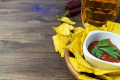 Nachos corn chips with classic tomato salsa. Fresh cold beer is perfect with savory snacks.  Stock Images