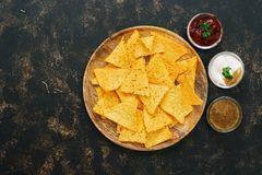 Nachos corn chips with variety of sauces on rustic dark background. The view from the top, place for text. Stock Photos