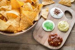 Nachos de fromage avec différents types de sauce Photos stock