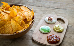 Nachos del queso con diversos tipos de salsa Imagenes de archivo