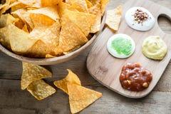 Nachos del queso con diversos tipos de salsa Imagen de archivo